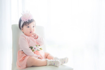 Little asian cute girl sitting on the chair in front of bright window