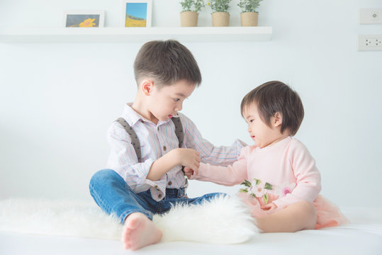 Little asian brother sitting with his sister on bed at home