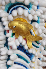 Chinese temple decoration depicting a gold fish appearing to swim amongst coral.