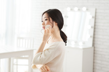 Portrait of young Korean woman applying face powder