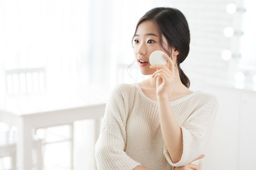 Beautiful Korean young woman applying layer of transparent face powder on her skin