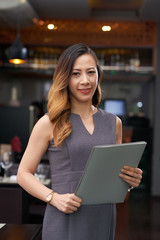 Portrait of pretty smiling restaurant owner with folder in hands
