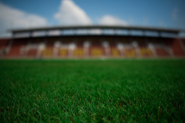Stadium background with a green grass pitch in the daytime