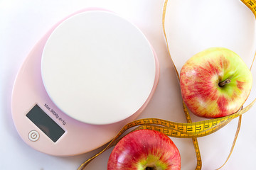 Diet concept. Apples and table top kitchen scales and measuring tape lie on a white background. Top view, close-up.