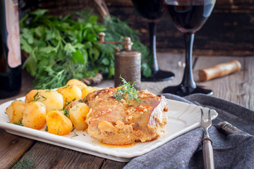 Baked turkey thigh meat with potatoes on a white dish, horizontal