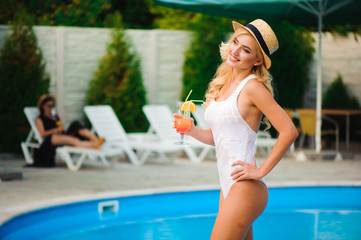 Attractive girl in white swimwear holding a cocktail  near the pool
