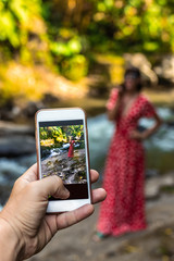 Man taking photo of woman in long red dress in nature of Bali island.