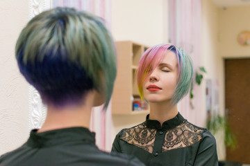 Woman 30-40 made coloring of hair in different colors and looks in a mirror in a hairdressing salon.