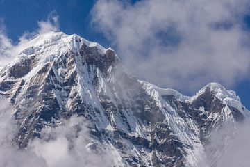 Wall Murals Nepal Annapurna South snowcapped summit surrounded by rising clouds in the Himalayas