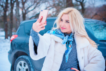 Winter holiday concept. Inspiration and fairy cold time. Woman in fashionable dress and fur coat at park take a selfie . Pretty nice lady outdoor, holiday days, snowy magical christmas time