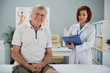 Happy aged man in office of young female chiropractor