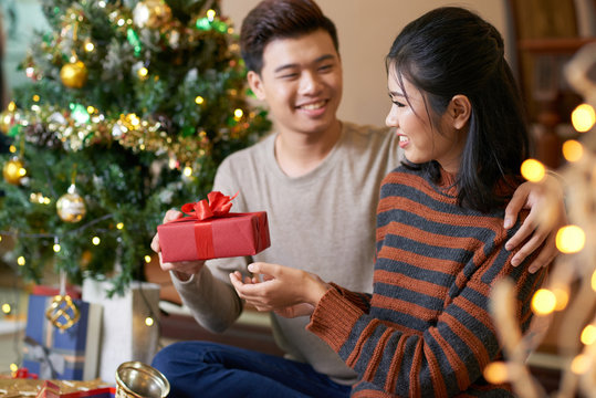 Young Vietnamese man giving Christmas present to his happy girlfriend