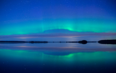 Wall Mural - Northern lights dancing over calm lake in Faenebofjarden national park in Sweden