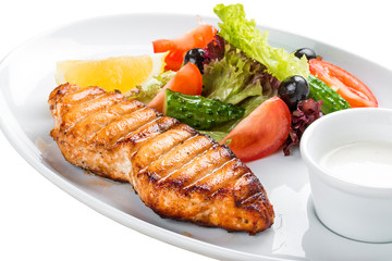 Grilled salmon steak with vegetables. On a white plate