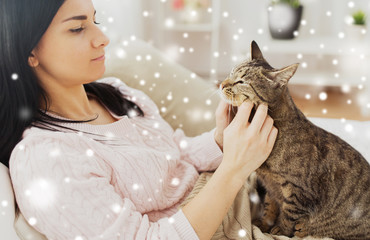 pets, hygge and winter concept - close up of woman with tabby cat in bed at home over snow