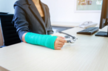blurred woman with broken hand and green cast  working on computer in office