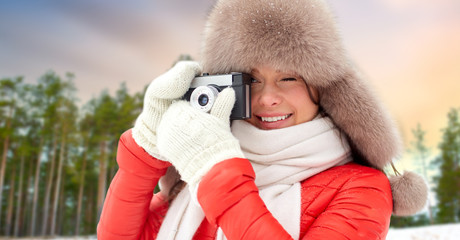photography, technology and season concept - happy woman in fur hat taking picture by film camera outdoors over winter forest background