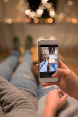 leisure, hygge and christmas concept - close up of couple taking foot selfie by smartphone and garland lights at home