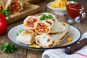 Burrito with ground beef and vegetables on a plate