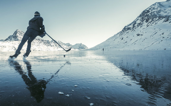 Beautiful view of the winter lake in the mountains. Clearing ice and winter mood, ice hockey player with ice skating in nature on frozen lake Lago Bianco - Switzerland