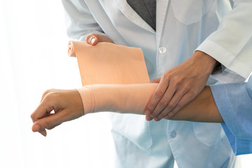 Doctor warpping an elastic compression bandage to the patient