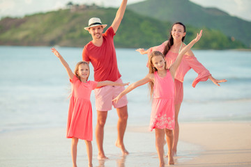 Happy family with kids walk on the beach at sunset