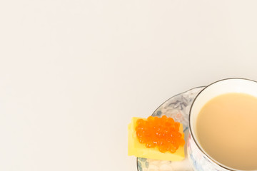 coffee, black or with milk, next to caviar on cheese, on a saucer