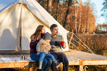 Happy family drinking coffee while sitting near canvas bell tent in a forest