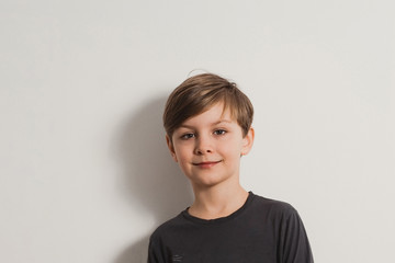 a closeup portrait of a smiling cute boy in a grey shirt, leaning on the white wall