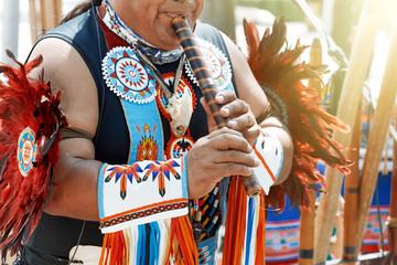 Peruvian man  plays the flute.