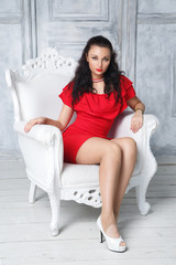 A beautiful woman in a red dress is sitting in an elegant armchair.