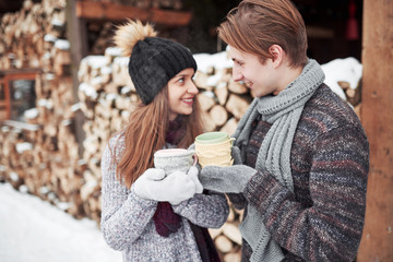 christmas happy couple in love embrace in snowy winter cold forest, copy space, new year party celebration, holiday and vacation, travel, love and relations