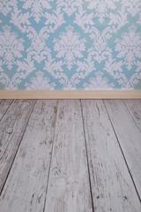 Blue damask wallpaper and white wooden floor