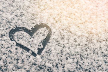 Finger-drawn heart on a snow-covered window