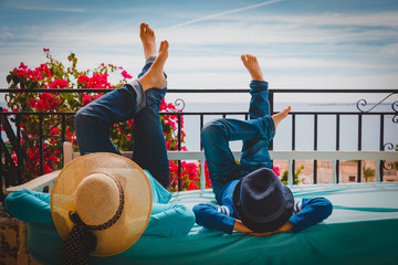 mother and son relax on balcony terrace with sea view, comfort