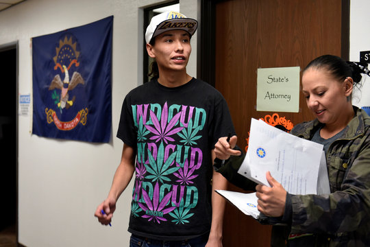 Terrell Elk waits with Desiree McArdel to get an absentee ballot form in the Sioux County Court House on the Standing Rock Reservation in Fort Yates