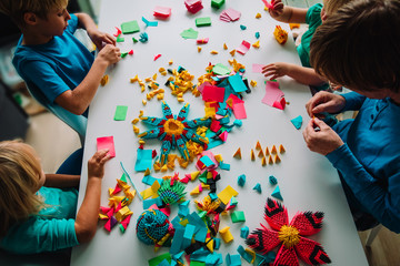 teacher and kids making origami crafts with paper