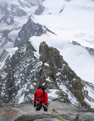 mountain climber rappelling off a high alpine rocky and snow peak