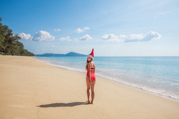 Happy young woman with long hair in red swimsuit and santa claus hat standing back on the tropical paradise beach by the sea with beautiful blue water and blue sky on Phuket island,Thailand