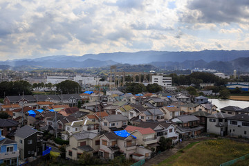 Aerial view of blue tarps on roofs in neighborhood hard hit by typhoon causing damage