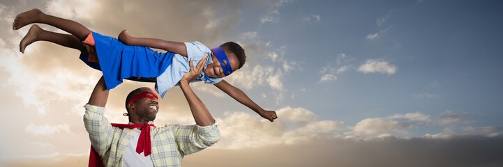Composite image of father and son pretending to be superhero