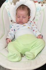 Cute newborn baby boy, sleeping in a swing