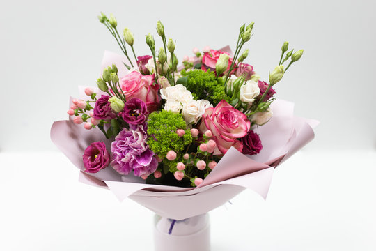Beautiful bouquet in pink paper on a light background