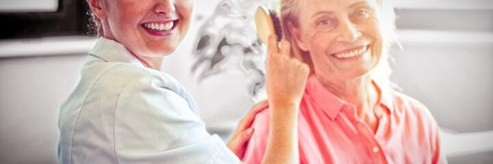 Female nurse combing hair of senior woman
