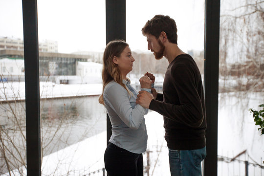 Side view of man holding arms of young woman violently having argument against window