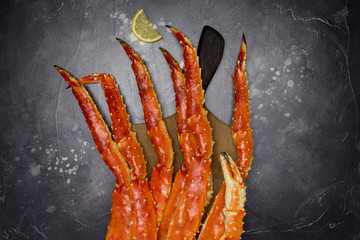 King Crab claw with lemon at wood board on black background