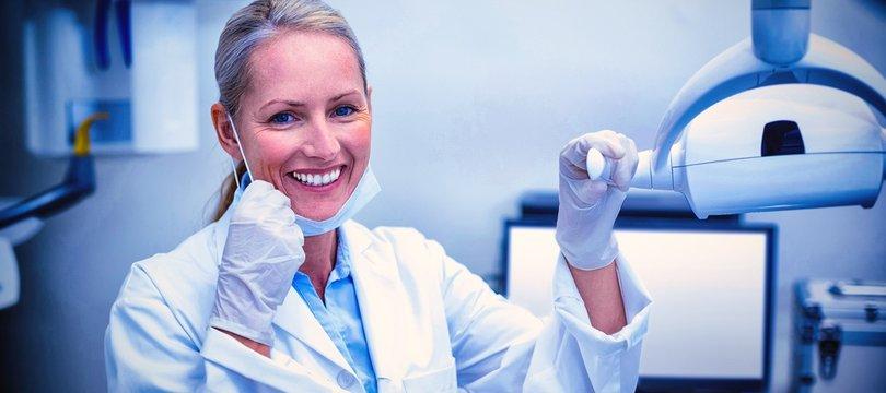 Female dentist holding dental lights