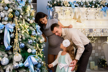 Family decorating a Christmas tree. Young man with his daughter helping her decorate the Christmas tree.