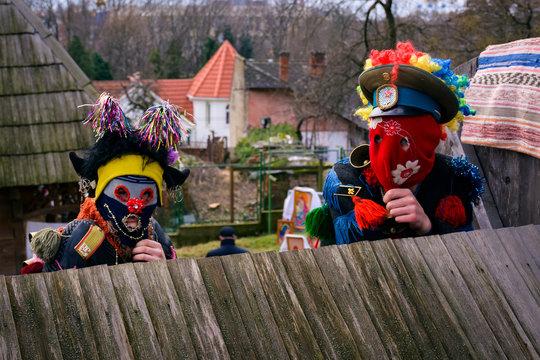 Uzhgorod, Ukraine - Jan 13, 2018: Vasylya festival celebrating in Museum of Folk Architecture and Life. representatives from Tyachiv region dressed as clowns scare visitors
