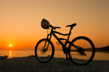 Silhouette of mountain bike on sunset at the seacoast
